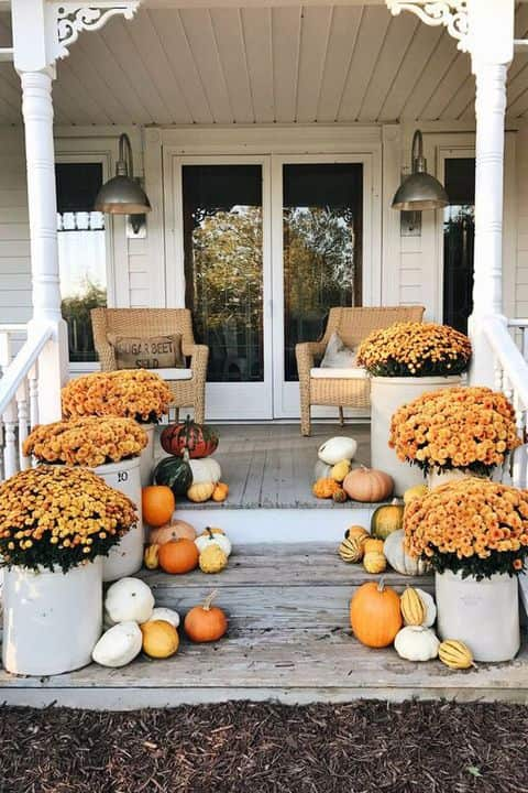 fall decor for front porch with orange mums and umpkins