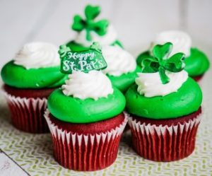 red cupcakes in white paper with green and white frosting topped with shamrocks for st patricks day