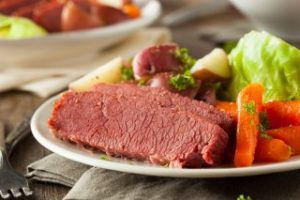 sliced corned beef on plate with carrots, cabbage, and red potatoes